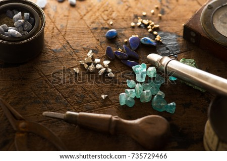 Exploring mining, and inspecting gems. Treasure hunting. Gold and gems on rough wooden surface. #735729466