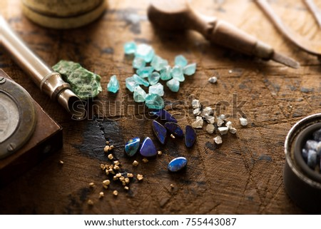 Exploring mining, and inspecting gems. Treasure hunting. Gold and gems on rough wooden surface. #755443087
