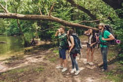 Exploring, researches and expedition concept. Four tourists are hiking near the river in a wild spring wood, guy is looking in the binoculars, jungle trails