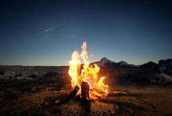 Exploring the wilderness in summer. A glowing camp fire at dusk providing comfort and light to appreciate nature, good times and the night sky full of stars. Photo composite.