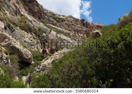 Exploring Wied Babu, at Wied iz-Zurrieq, green rocky valley, leading down to the azure turquoise water of the Blue Grotto, Zurrieq, Malta, May 2017