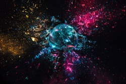 explosion of a glass ball with colored lights, black background. high speed photography.