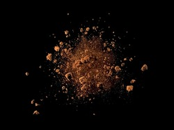 Explosion of cocoa powder with lumps on black background