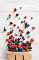 Explosion of different berries. Photo of strawberry, blueberry, blackberry, raspberry in basket on white wooden table. Top view. High resolution product.