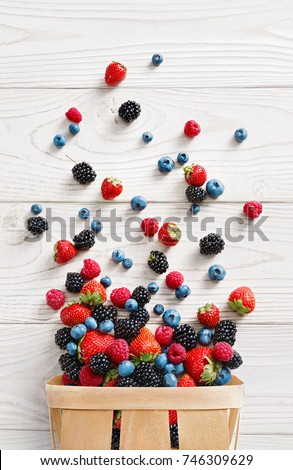 Explosion of different berries. Photo of strawberry, blueberry, blackberry, raspberry in basket on white wooden table. Top view. High resolution product.  #746309629