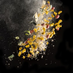 Explosion of ingredients for Italian kitchen (tomato, pasta, cheese, chopping board and knife) isolated in the air on black background