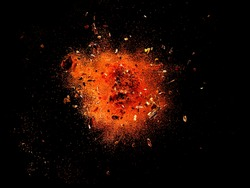 Explosion of red cayenne pepper with flakes and seeds on black background