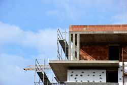 exposed concrete column and slab structure. building frame during construction. steel scaffolding. red clay block infill. construction concept. cantilevered balcony. styrofoam insulation. blue sky