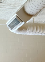 Exposed corrugated duct work and vent register hanging from a ceiling.