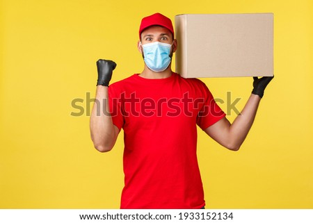 Express delivery during pandemic, covid-19, safe shipping, shopping concept. Rejoicing happy courier fist pump, holding box on shoulder, deliver successfully, chanting saying yes, wear medical mask