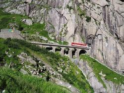 Express St. Gotthard train on Teufelsbruecke, Devil's railway bridge and tunnel, Andermatt in Switzerland, swiss Alps, alpine rocky mountains landscape scenery in 2017 warm summer day, Europe on July.