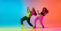 Express yourself. Modern dance style. Two beautiful young girl practising hip-hop on gradient blue orange background in neon. Youth culture. Concept of movement, active lifestyle, hobby, ad