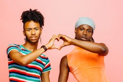 Expressing love/ Portrait of two men holding hands and making a heart shape with their hands, isolated on pink studio background