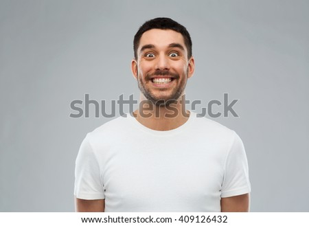 expression and people concept - man with funny face over gray background