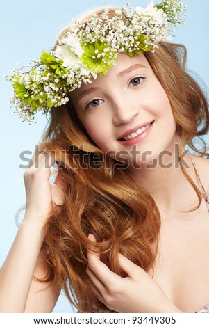 expression portrait of beautiful healthy smiling redhead teen girl in garland on blue