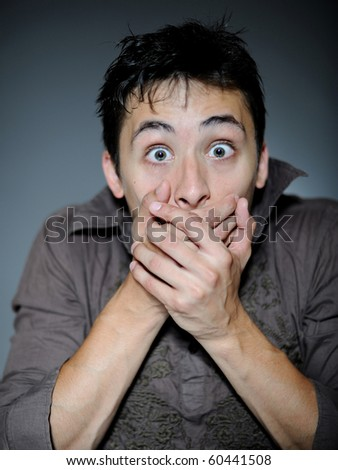 Expressions. Handsome young man feeling fear and shock  closing mouth with hands