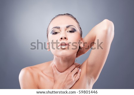 ... brunette woman looking at camera strangling herself - stock photo