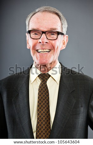 Expressive good looking senior man in dark suit against grey wall. Wearing glasses. Funny and characteristic. Well dressed. Studio shot.