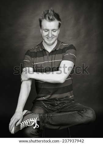 Expressive handsome young man sits in the studio - black and white image, dark background