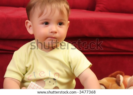 Expressive little blond baby boy gesticulate while reading a child book