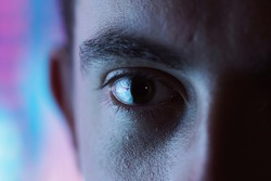 Expressive look - closeup of an eye with blurred blue and pink neon light background and high contrast