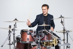 Expressive young drummer playing at the drums with drum stick