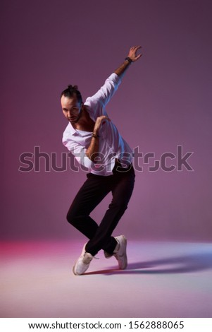 Expressive young man showing dance element, stands on tiptoe, raises hand up, looks away with impressive eyes, expressing in full body, isolated on pink background, studio shot #1562888065