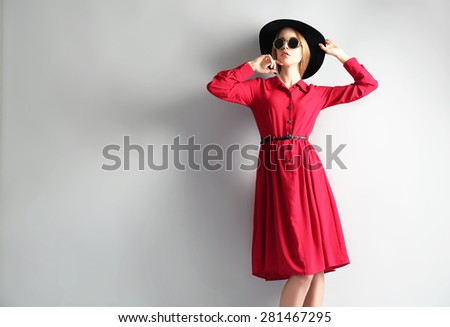 Stock Photo Expressive young model in red dress, black hat and sunglasses on gray background