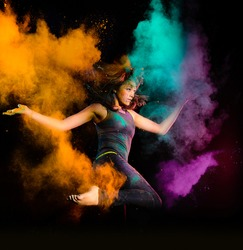 Expressive young woman makes a high jump with a explosion of dry colorful holi powder. Holi colour splash