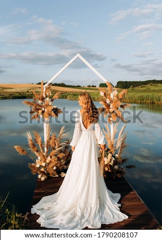 Exquisite bride standing with her back near  wedding arch. Wedding ceremony Stockfoto ©