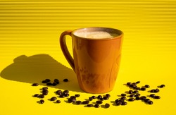 Exquisite freshly made sparkling coffee inside a brown cup with coffee beans scattered on a yellow table with a yellow background reflecting a black shadow on the side.