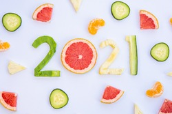 Exquisite fruits cut in the shape of the new year 2021 on a white table decorated with pieces of different fruits around it.