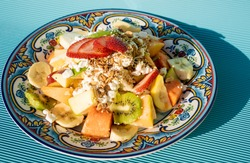 Exquisite healthy fruit salad with melon, kiwi, pineapple, green and red apple, guava, strawberries and banana cut with granola and cheese on top on a plate on a blue table.