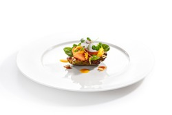 Exquisite serving avocado with mozzarella cream and dried tomato jam on white restaurant plate isolated. High cuisine restaurent dish with delicious vegetables and greens in modern minimalist style