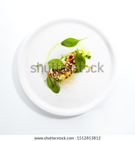 Exquisite serving avocado with mozzarella cream and dried tomato jam on white restaurant plate isolated. High cuisine restaurent exotic dessert with alligator pear in minimalist style topview