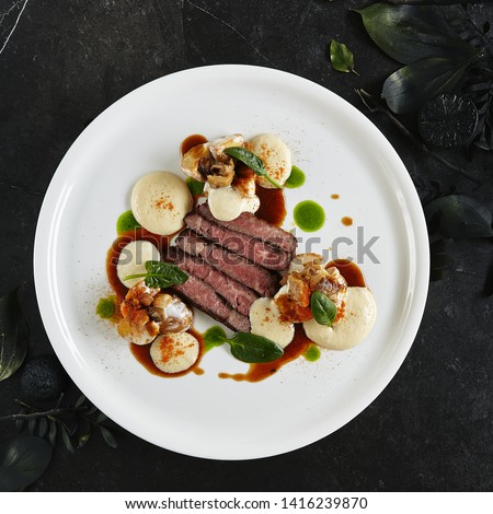 Exquisite Serving White Restaurant Plate of Black Angus Beef Fillet with Warm Potatoes in Cheese Sauce and Mushroom Espuma. Luxury Molecular Dish with Sliced Veal Meat on Black Marble Backdrop