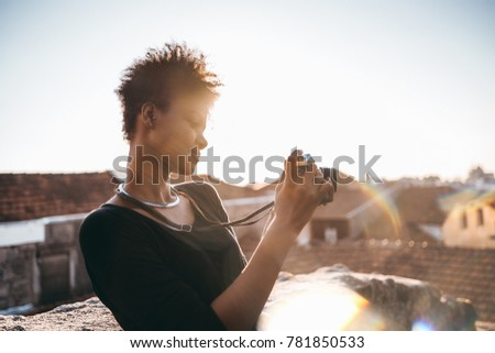 Exquisite young curly Brazilian female photographer is taking panoramic picture of Porto city while standing on the roof of a house and using old vintage film photo camera; backlighted by summer sun