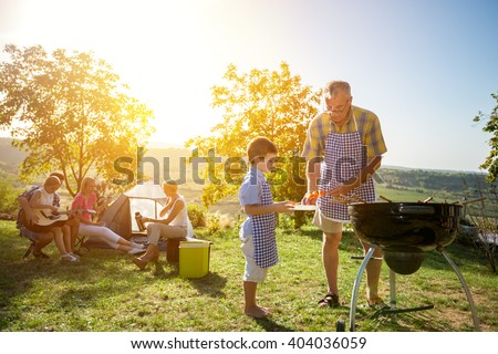 Extended family cooking barbecue in park