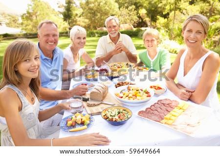 Extended Family Enjoying Meal In Garden