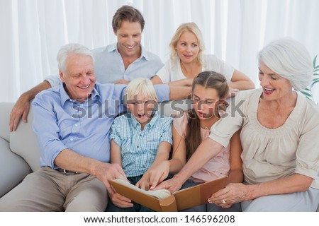 Extended family looking at their album photo in the living room