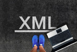Extensible Markup Language. man legs in sneakers standing next to laptop and word XML