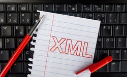 Extensible Markup Language. Word XML on laptop and paper with pencil