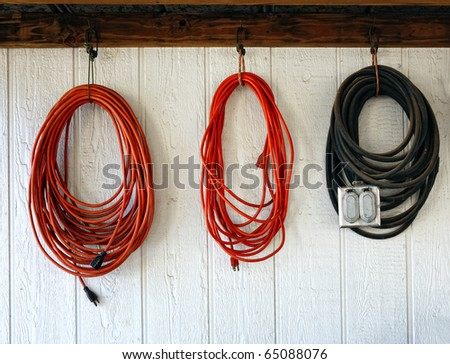 Extension power cords on the wall of working shop