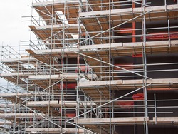Extensive scaffolding providing platforms for work in progress on a new apartment block UK