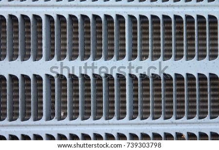 Exterior Air Conditioner Vents - Close up photograph of vents on an exterior air conditioner unit.  Weather spots on the metal around the vents.  #739303798