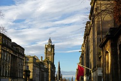 Exterior architecture and decoration of Princess street with cloudy blue sky ,the main shopping road in the capital of Edinburgh town ,Scotland