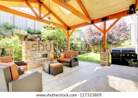 Exterior covered patio with fireplace and furniture. Wood ceiling with skylights.