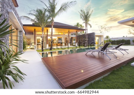 Exterior design of spacious modern luxury pool villa. Feature wooden decking, sunbed, big swimming pool and greenery garden , home , house