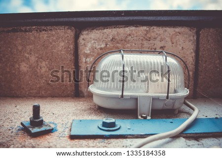 Exterior electric light fitting on bricks with plastic cover protected by wire frame and cord leading towards the camera #1335184358