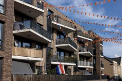 Exterior facades with street decoration with orange flags in support of the Dutch national soccer team during the European Championship in 2021. Supporters and traditional Holland festivities concept.